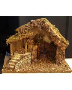 Kerststal van hout met stro baaltje en trap naar plateau